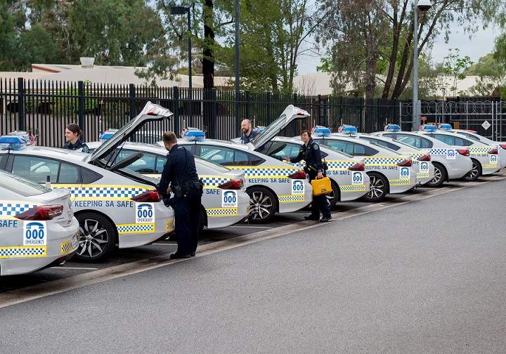 Police officers load up patrol cars as part of District Policing Stage 2